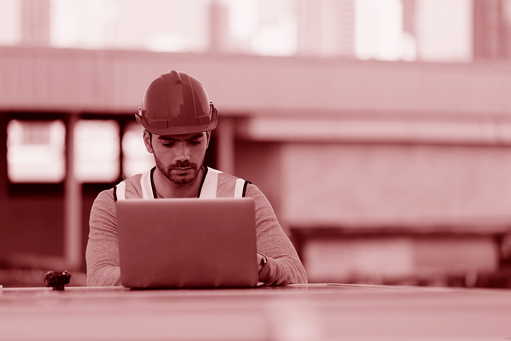 Construction worker looking at a laptop